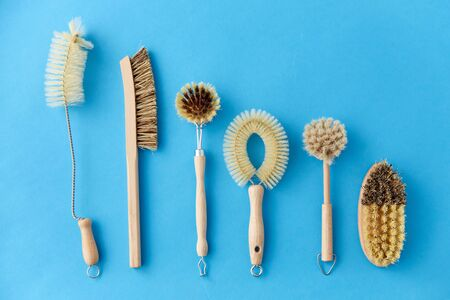 natural cleaning stuff, sustainability and eco living concept - different brushes with wooden handles on blue background