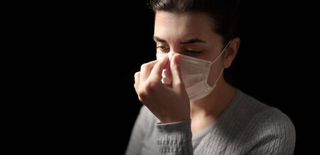 sick woman adjusting protective medical face mask