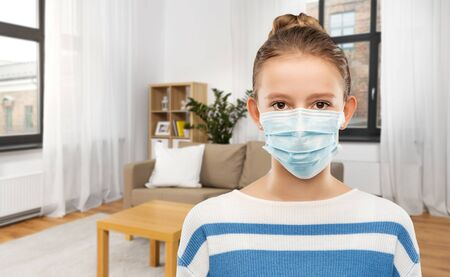 teenage girl in protective medical mask at home 写真素材