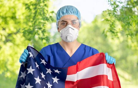 doctor in goggles and mask holding flag of america
