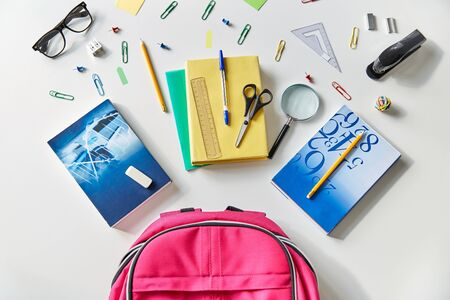 pink backpack with books and school supplies
