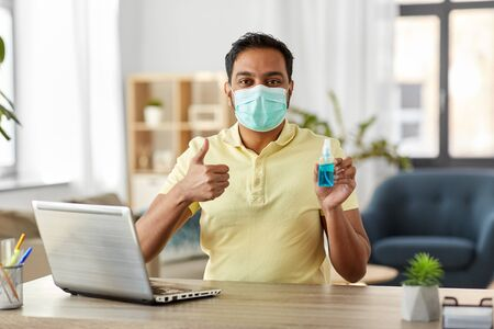 man in mask with hand sanitizer at home office