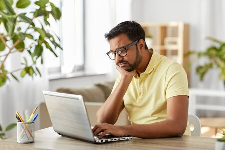 bored man with laptop working at home office