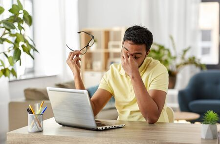 tired man with laptop working at home office