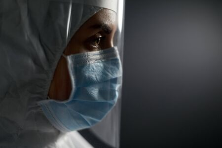 doctor in protective wear, mask and face shield