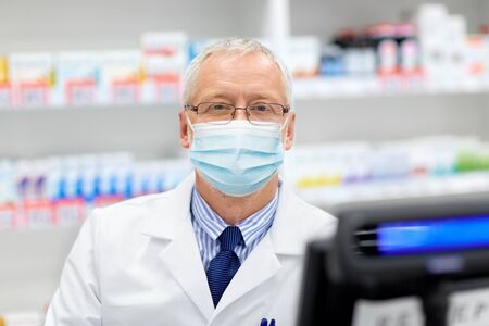 senior apothecary in mask at pharmacy
