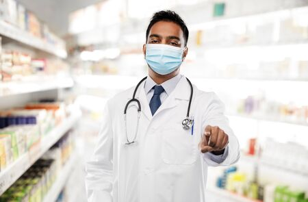 indian male doctor in mask pointing finger to you