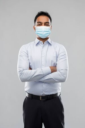 indian businessman in mask over grey background