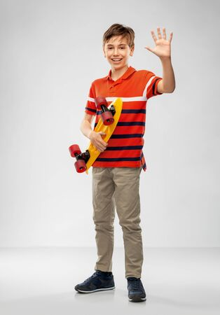 smiling boy with short skateboard waving hand