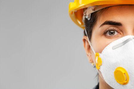 female worker or builder in helmet and respirator Reklamní fotografie
