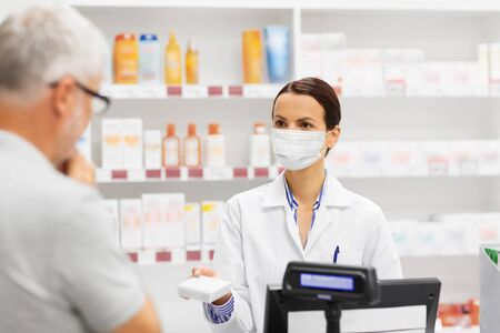 apothecary in mask showing drug to man at pharmacy