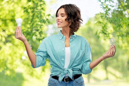 smiling woman comparing different light bulbs Standard-Bild - 147426743