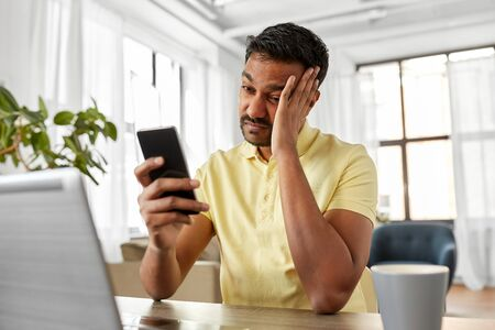 indian man with smartphone at home office