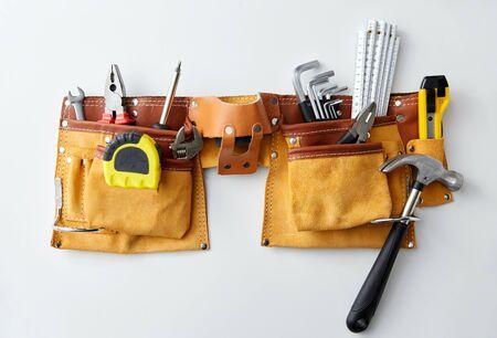 Différents outils de travail en ceinture sur fond blanc
