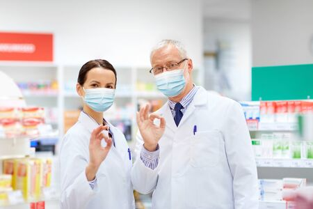 apothecaries in masks at pharmacy showing ok