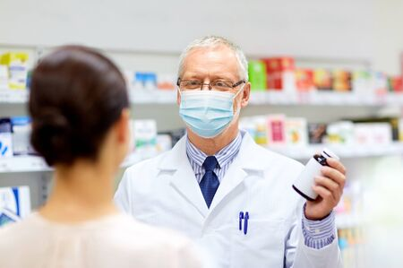 apothecary in mask with drug and woman at pharmacy