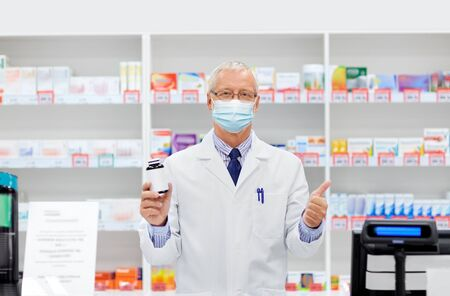senior apothecary in mask with drug at pharmacy