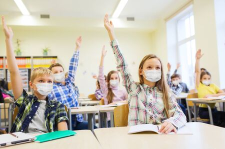 group of students in masks raising hands at school