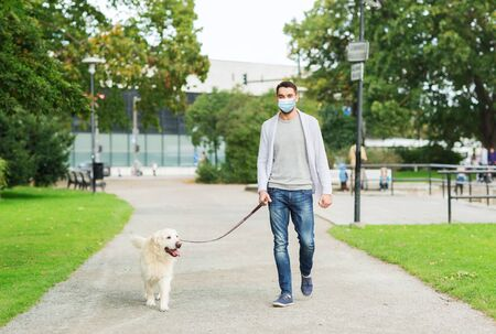 man in mask with labrador dog walking in city