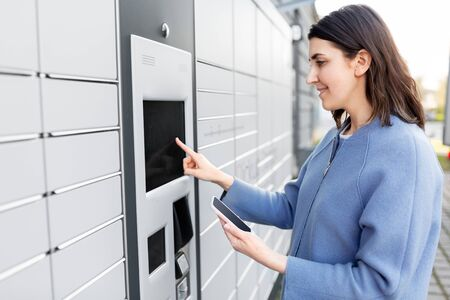 woman with smartphone at automated parcel machine