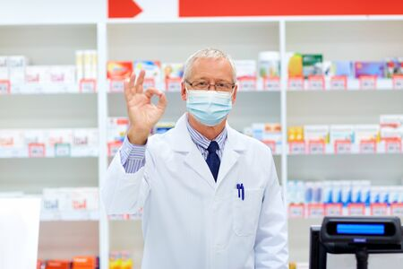 senior apothecary in mask at pharmacy showing ok