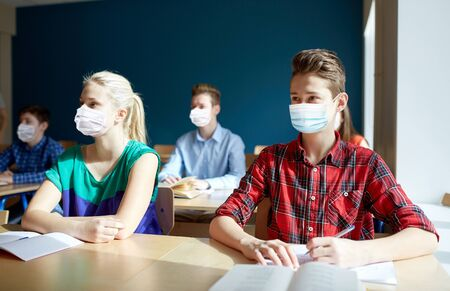 group of students in masks at school lesson