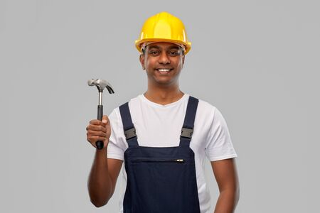 happy smiling indian worker or builder with hammer