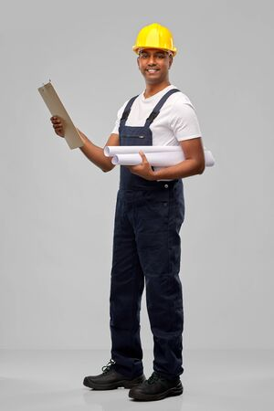 happy indian builder with blueprint and clipboard