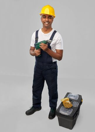 happy indian builder in helmet with electric drill Stock Photo
