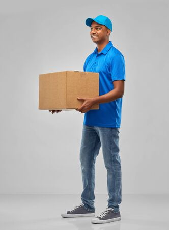 happy indian delivery man with parcel box in blue Stock Photo