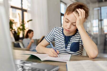 student boy with book writing to notebook at home
