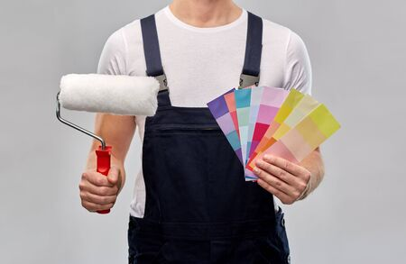 close up of painter with roller and color charts