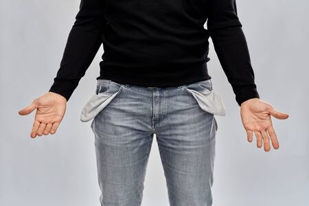 close up of man showing empty pockets over grey