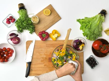 hands cooking vegetable salad on kitchen table Stock Photo