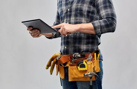 male builder with tablet pc and working tools