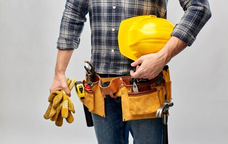 repair, construction and building - male worker or builder with helmet and working tools on belt over grey background