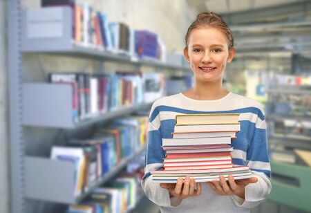 smiling teenage student girl with books at library