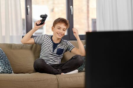 happy boy with gamepad playing video game at home Stock Photo