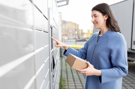 smiling woman with box at automated parcel machine