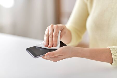 close up of hands cleaning smartphone with tissue