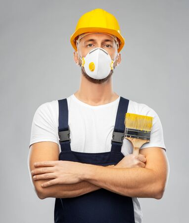 male worker or builder in helmet and respirator Stock Photo