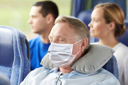 senior man in mask sleeping in travel bus
