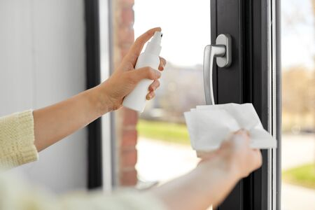 woman cleaning window handle with sanitizer tissue