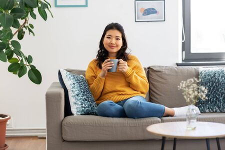 smiling asian young woman drinking coffee at home