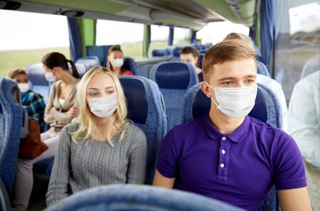 couple or passengers in masks in travel bus