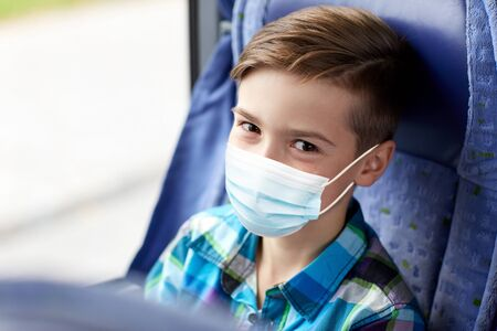 boy in mask sitting in travel bus or train