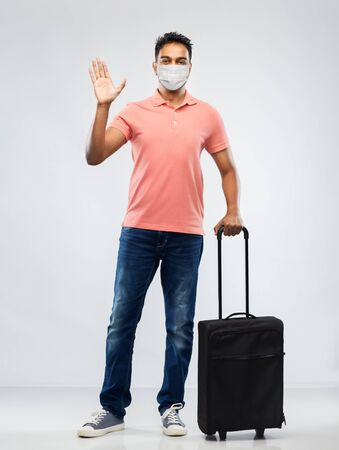 indian man in mask with travel bag waving hand Stock Photo