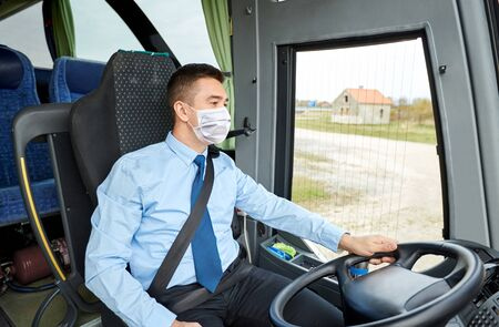 bus driver in mask talking to microphone Archivio Fotografico