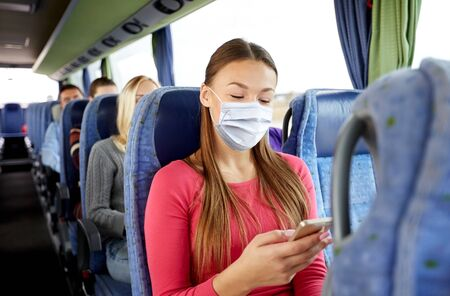 woman in mask with smartphone in travel bus Standard-Bild