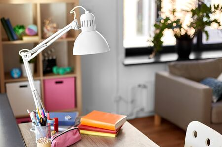interior, home and education concept - room with lamp and school supplies on table Foto de archivo